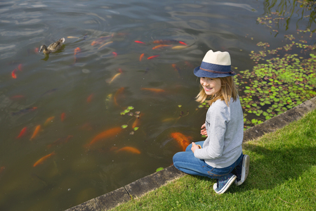 small girl: Happy girl teenager feeding fishes in a garden pond