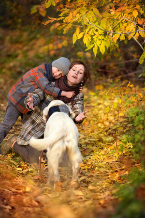 dog park: Happy mom and her son with golden retriever in autumn park