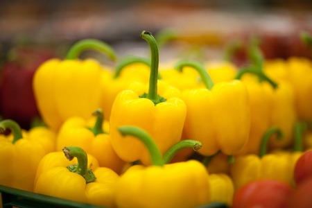Red and yellow bell peppers on a counter in the supermarket, natural background. Close up and full frame view of peppers.