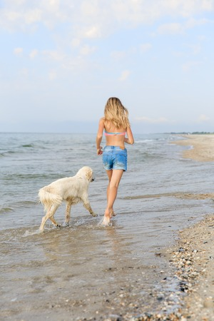Teenage girl running along a beach shore with her golden retriever during the early morning.