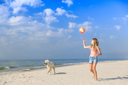 happy girl playing with a dog on the beach