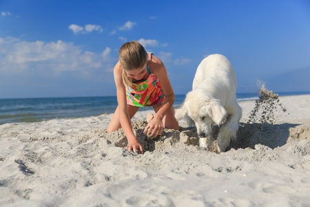 Beautiful girl playing with a playful Golden retriever on the sea shore. Outdoor portrait. series