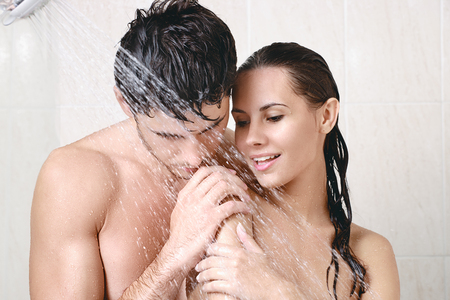Young beautiful couple washing in the shower Stock Photo