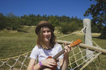 Beautiful girl playing ukulele - hawaiian guitar in hammock