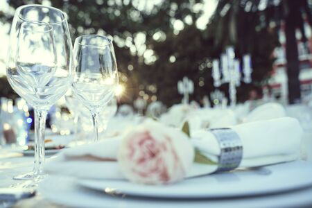 Table setting for garden banquet with expensive table cloth, silverware, and wine glasses and with flowers
