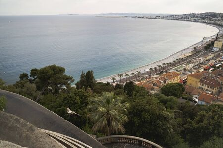 Luxury resort of French riviera. Beautiful view at city of Nice in France. Mediterranean sea, public beach, famous quay, palms and houses of Nice.