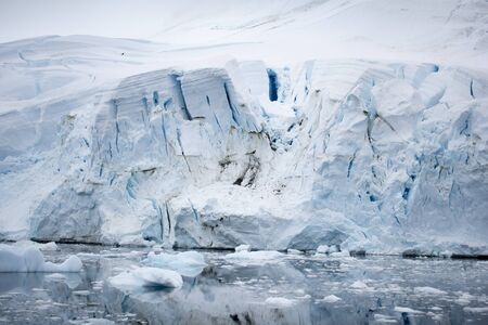 Icebergs floating. Ices and volcanic ash. Glacier lagoon. Melting ice. Antarctic peninsula, Antarctica. Volcanic ash on the arctic ice. Ice age glacier crevasse melting fast. Global warming. The edge of a glacier