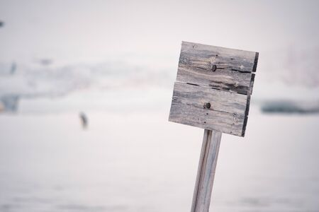 Pointer made of wood on a background of harsh nature of Antarctica. The pointer is fixed to a column, and there is no label on the pointer.