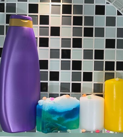 Body care product in a bottle of violet color. Hair shampoo and handmade soap on the shelf. Shelf in the bathroom.