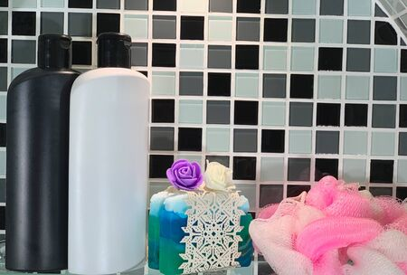 Shampoo in bottles of white and black color.Hair shampoo and handmade soap on the shelf. Shelf in the bathroom.