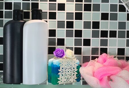 Skin care product in bottles. Hair shampoo and handmade soap on a shelf. Bath sponge.