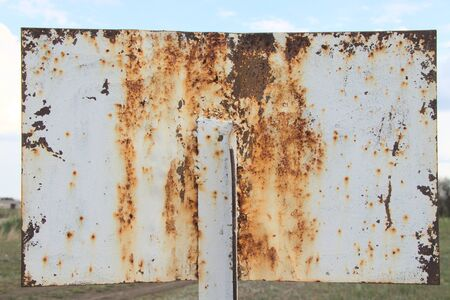 Old metal plate, white. Rusty plate for text. Old weathered metal, outdoors.