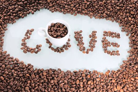 Coffee beans, love of coffee. Background with text love .Coffee white cup on the table. Hot drink in a white bowl.
