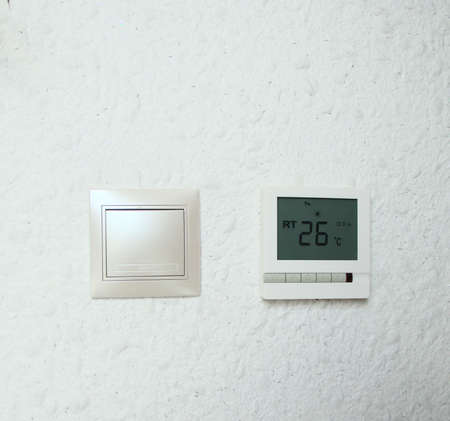 Temperature regulator of temperature of a floor. The sensor of a temperature mode, in the smart house. The switch plastic for light, white color.