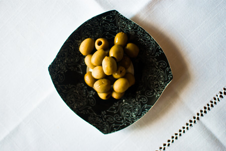 Black vintage plate, green-yellow olives, and white tablecloth