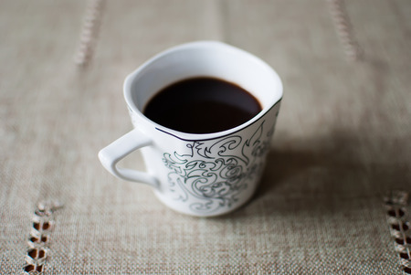 cosily: White cup of black coffee on a tablecloth