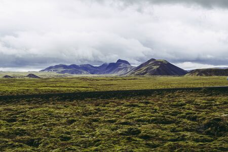 Endless landscapes of Iceland. Pale green grass and misty mountains under gray rainy clouds.