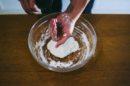 Pizaiolo pouring olive oil into the pizza dough
