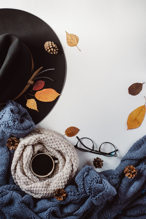 Flat lay-out of the leaves and tartan textured blue sweater on a white background with a cup of coffee, glasses and a hat. Autumn concept.