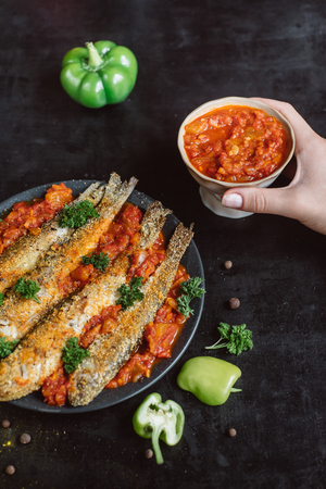 Fried fish in a plate with tomato sauce, greens and peppers on a dark background
