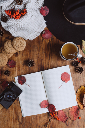 Flat lay-out of autumn leaves and tartan textured sweater on a wooden background with a cup of tea. Autumn or Winter concept.