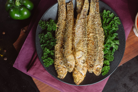 Fried fish in a plate with tomato sauce, greens and peppers on a wooden board and a dark background