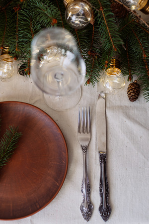 Table with Christmas decorations and green spruce branches