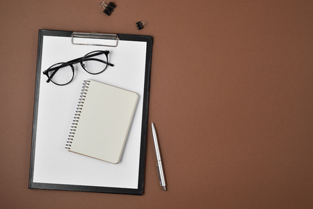 Mock up workspace with blank clip board, office supplies, pen, notepad and eyeglasses on brown background. Flat lay, top view, copy space
