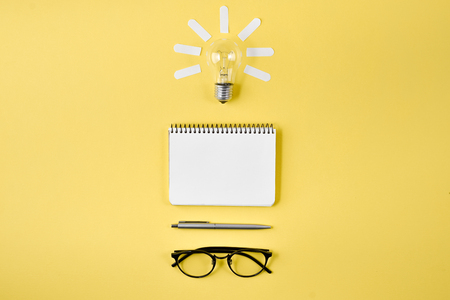 Financial planning table top with pen, notepad, eyeglasses and light bulb on yellow background. Concept brainstorming and new idea