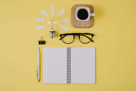 Creative flat lay concept top view of workspace desk styled design office supplies with pen, notepad, eyeglasses, cup coffee and light bulb on a yellow background. Concept brainstorming