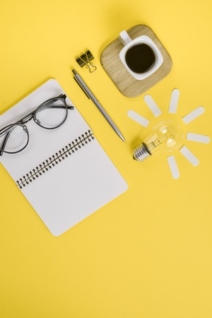 Top view flat lay of workspace desk styled design office supplies with pen, notepad, eyeglasses, cup coffee and light bulb on a yellow color paper background minimal style. Concept brainstorming Фото со стока