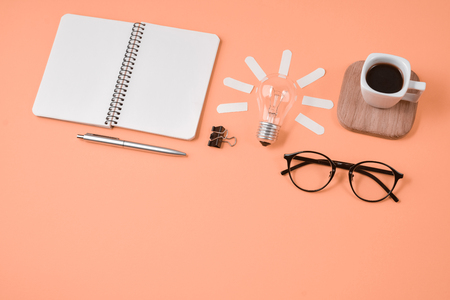 Top view flat lay of workspace desk styled design office supplies with pen, notepad, eyeglasses, cup coffee and light bulb on a orange color paper background minimal style. Concept brainstorming