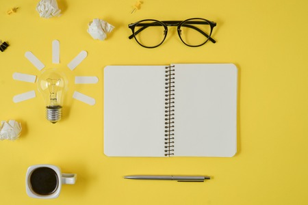 Office workspace with blank clip board, office supplies, pen, notepad, eyeglasses, coffee cup and light bulb on yellow background. Concept brainstorming and new idea
