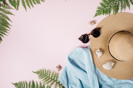 Feminine summer fashion composition with blouse, hat, sunglasses, fern, seashell on pink background. Flat lay, top view minimalist clothes collage. Travel vacation concept. Summer background.