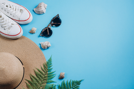 Flat lay traveler accessories on blue background with tropical fern leaf branches, footwear, hat and seashell. Top view travel or vacation concept. Summer background