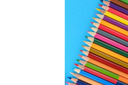 Creative flat lay back to school concept with colored pencils on blue and white background. Minimal concept art. Top view, copy space.
