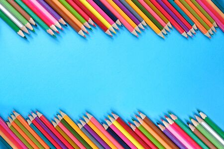 School concept. Creative composition of many color pencils on blue background. Flat lay, top view, copy space.