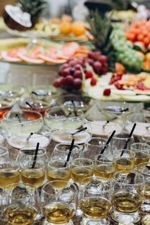 Festive table with cold exotic alcoholic beverages, cocktails and fruits. Celebration or other event