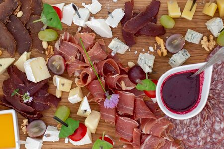 Large selection of food with cold snacks, salads, cold meats, cheese and jam served. Variety of tasty delicious snacks on the table. Wedding reception