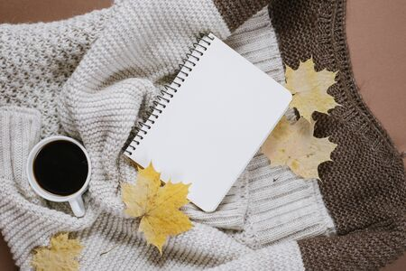 Autumn composition. Knitted sweater, cup of coffee, notebook, autumn maple leaves on brown background. Flat lay, top view, copy space.