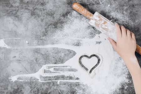 Baking background. Girl hands keep rolling pin and heart of flour on gray table with copy space, top view. Valentine's Day Stockfoto