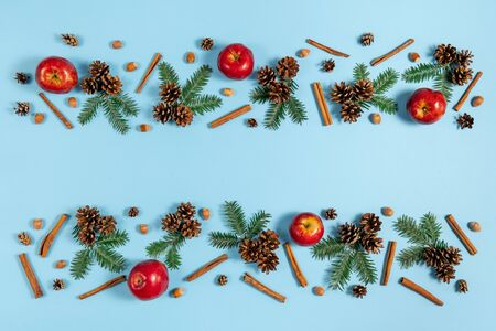 Christmas composition. Tree branches, pine, red apple, acorn and cinnamon on pastel blue background. Christmas, winter, new year concept. Flat lay, top view, copy space