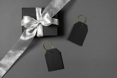 Gift box wrapped in black paper with silver ribbon and price tags on gray background. Copy space and top view. Black friday box gift present isolated.