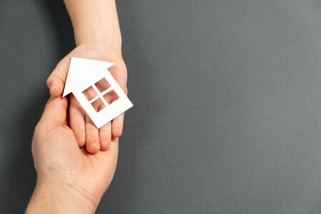Close up horizontal image of female and child hands holding white paper house on gray background. Family home and real estate concept. Flat lay, copy space