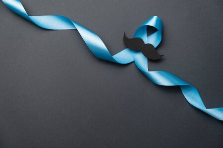 Light blue ribbon with mustache on black background. Prostate Cancer Awareness, Movember Men's health awareness. Healthcare, International men, Father and World cancer day concept.