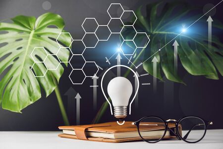 Close up of home office desk table workspace with notebook, light bulb with hologram, monstera leaves and eyeglasses on red background. Copy space mockup template. Brainstorm teamwork meeting concept
