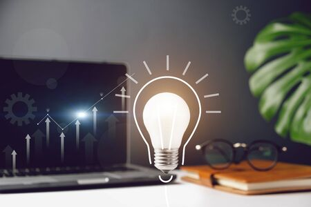 Light bulb with technology theme hologram, laptop, monstera leaves, eyeglasses and notebook with copy space on grey background minimal style. Concept brainstorming and new ideas.