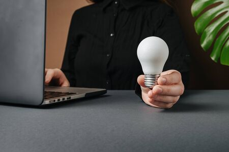 Close up front view young woman holding white light bulb, sitting at desk near pc, ideas of new ideas with innovative technology and creativity. Website header design with copy space for text
