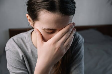 Sad tired unhealthy young woman sitting on bed in living room at home with closed eyes, holding head with hand, suffering from strong sudden headache or migraine, grief sorrow concept.