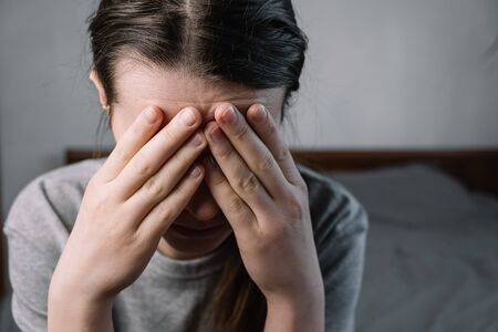 Close up images of thoughtful insecure young woman touching forehead having headache migraine or depression, stressed frustrated anxious lady doubting deciding troubled with grief sorrow concept.
